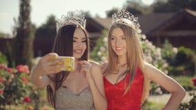 Dos hembras jovenes atractivas en vestidos de noche hermosos almacen de metraje de vídeo