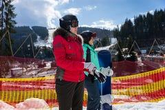 Dos hembras jovenes en traje de esquí, con el casco y las gafas del esquí se colocan Foto de archivo libre de regalías
