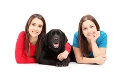 Dos hembras jovenes que mienten y que presentan con un perro Foto de archivo