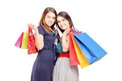 Dos hembras jovenes que presentan con los bolsos de compras Foto de archivo libre de regalías