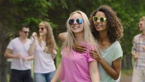 Dos hembras multirraciales que bailan feliz al aire libre, gente joven que disfruta del partido metrajes