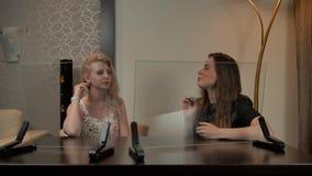 Dos hembras que miran la exhibición transparente almacen de metraje de vídeo