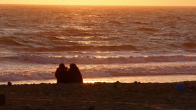 Dos hembras que se sientan en la playa en la puesta del sol almacen de video