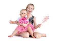 dos hermanas 8 años y bebés de 11 meses con el caramelo Foto de archivo