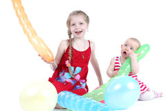 Dos hermanas 8 años y bebés de 11 meses con impulso del aire Foto de archivo libre de regalías