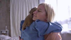 Dos hermanas abrazan y miran uno a con dulzura cerca de la ventana de la casa almacen de metraje de vídeo