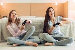 Dos hermanas adolescentes que juegan al videojuego en dormitorio Fotografía de archivo libre de regalías