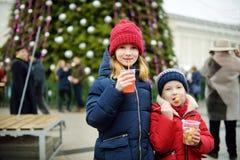 Dos hermanas adorables que beben el zumo de manzana caliente en mercado tradicional de la Navidad imagenes de archivo