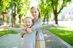 Dos hermanas adorables que ríen y que abrazan en día de verano caliente y soleado en un parque foto de archivo libre de regalías