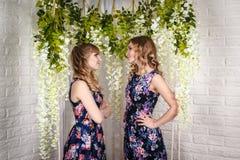 Dos hermanas agradables con el pelo rubio y las flores alrededor Fotografía de archivo