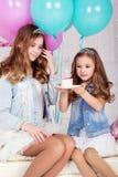 Dos hermanas bonitas con la torta de cumpleaños Imagen de archivo