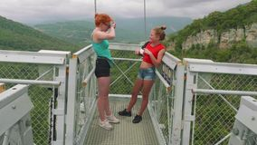 Dos hermanas caucásicas ríen y hablan en un alto de puente colgante en las montañas Pelo rojo y rubio metrajes
