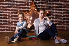 Dos hermanas con el monopatín en estudio Fotografía de archivo