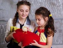 Dos hermanas con el pollo del bebé Imagen de archivo libre de regalías