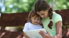 Dos hermanas con la tableta blanca se sientan en el banco del oscilación en jardín metrajes