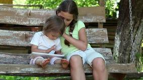 Dos hermanas con la tableta se sientan en banco del oscilación almacen de video