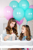 Dos hermanas con la torta y los globos, concepto del cumpleaños Imágenes de archivo libres de regalías