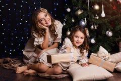 Dos hermanas con los regalos de la Navidad en casa Fotos de archivo