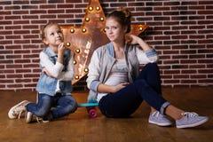 Dos hermanas de las muchachas con el monopatín en casa Imágenes de archivo libres de regalías