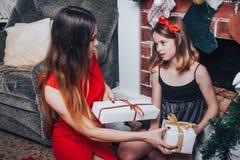 Dos hermanas de las muchachas con la caja de regalo tienen relajarse y diversión en el cuarto adornado por la Navidad y el Año Nu Foto de archivo