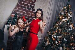 Dos hermanas de las muchachas tienen relajarse y diversión en un cuarto adornado por la Navidad y el Año Nuevo Imágenes de archivo libres de regalías