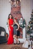 Dos hermanas de las muchachas tienen relajarse y diversión en un cuarto adornado por la Navidad y el Año Nuevo Fotos de archivo libres de regalías