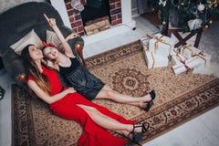 Dos hermanas de las muchachas tienen relajarse y diversión en un cuarto adornado por la Navidad y el Año Nuevo Foto de archivo libre de regalías