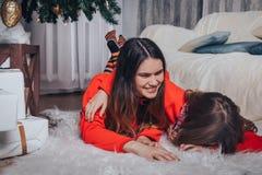 Dos hermanas de las muchachas tienen relajarse y diversión en un cuarto adornado por la Navidad y el Año Nuevo Imagen de archivo