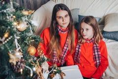 Dos hermanas de las muchachas tienen relajarse y diversión en un cuarto adornado por la Navidad y el Año Nuevo Fotos de archivo