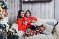 Dos hermanas de las muchachas tienen relajarse y diversión en un cuarto adornado por la Navidad y el Año Nuevo Imagen de archivo libre de regalías
