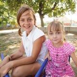 Dos hermanas en el carrusel Imagen de archivo libre de regalías