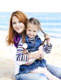 Dos hermanas en la playa en día asoleado del otoño Foto de archivo libre de regalías