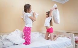 Dos hermanas en los pijamas que se divierten en la almohada que luchan en el dormitorio Imágenes de archivo libres de regalías