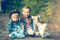 Dos hermanas en pcteres de ruedas Imagen de archivo libre de regalías