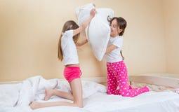 Dos hermanas en pijamas que luchan con las almohadas en cama Foto de archivo
