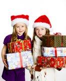 Dos hermanas en sombreros rojos de los sants con las cajas de regalo Fotografía de archivo