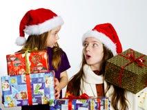 Dos hermanas en sombreros rojos de los sants con las cajas de regalo Foto de archivo libre de regalías
