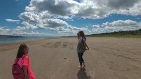Dos hermanas están caminando a lo largo de la playa