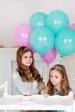 Dos hermanas están celebrando cumpleaños con la torta Fotos de archivo libres de regalías