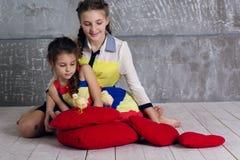 Dos hermanas están jugando con el pollo del bebé Foto de archivo libre de regalías