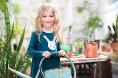 Dos hermanas están trasplantando las flores en potes en el invernadero Niñas con los rizos en vestidos verdes y cultivar un huert Imagen de archivo libre de regalías