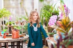 Dos hermanas están trasplantando las flores en potes en el invernadero Niñas con los rizos en vestidos verdes y cultivar un huert Imagen de archivo