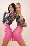 Dos hermanas felices que llevan los mismos vestidos brillantes Imagen de archivo