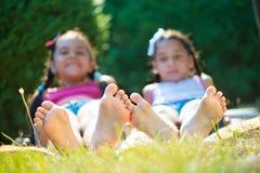 Dos hermanas felices que mienten en hierba verde Imagen de archivo