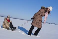 Dos hermanas felices sledding Fotos de archivo libres de regalías