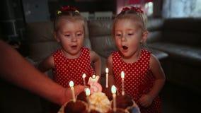 Dos hermanas gemelas encantadoras en vestidos rojos hermosos están esperando una torta con las velas ardientes Soplan velas y almacen de metraje de vídeo