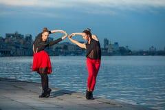 Dos hermanas gemelas hermosas jovenes están bailando danza waacking en el fondo de la ciudad cerca del río Imagen de archivo