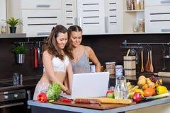 Dos hermanas gemelas que buscan receta de la ensalada en Internet Foto de archivo libre de regalías