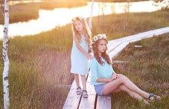 Dos hermanas hermosas que se colocan contra la perspectiva de un paisaje hermoso, paseo en el campo cerca de una charca en la pue Foto de archivo libre de regalías