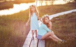 Dos hermanas hermosas que se colocan contra la perspectiva de un paisaje hermoso, paseo en el campo cerca de una charca en la pue Fotografía de archivo